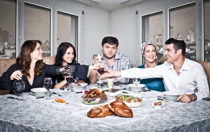 Elenco de la serie Srugim sentados frente a un comedor