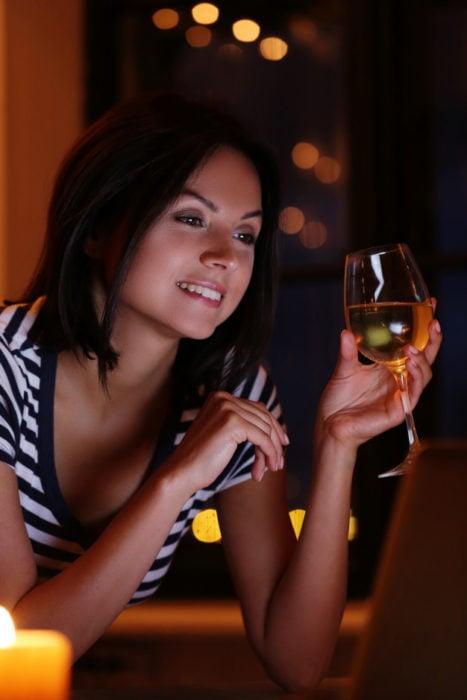 Chica frente a una computadora bebiendo una copa de vino tinto