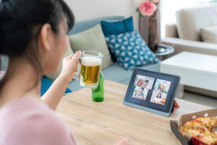 Grupo de chicas en videollamada haciendo una fiesta en línea comiendo pizza y bebiendo cerveza