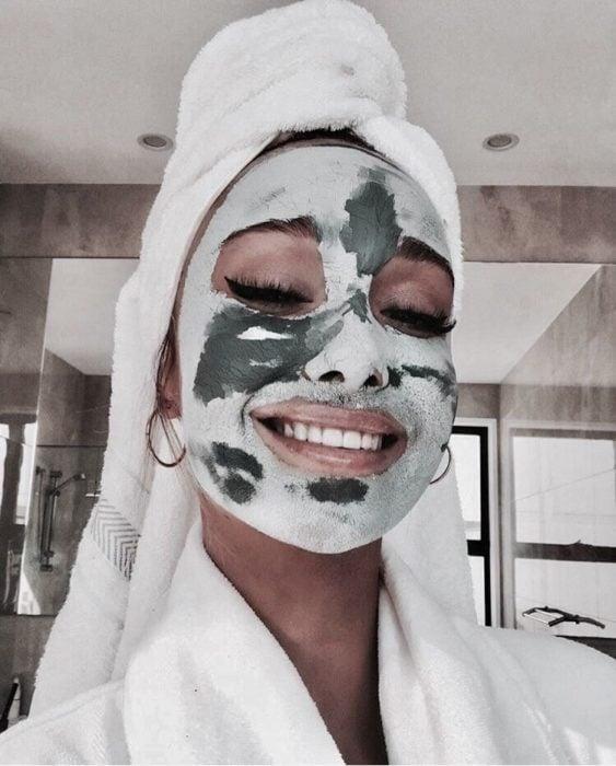 Chica tomando una selfie de lla con mascarilla de arcilla verde y una toalla sobre la cabeza