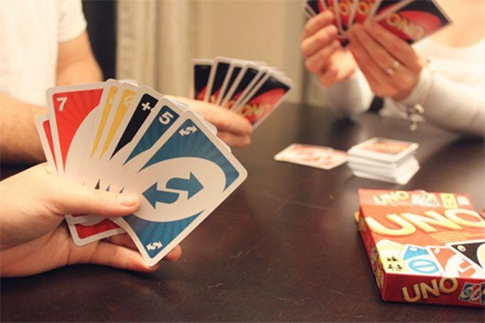 Grupo de personas reunidas alrededor de una mesa sosteniendo cartas del juego UNO