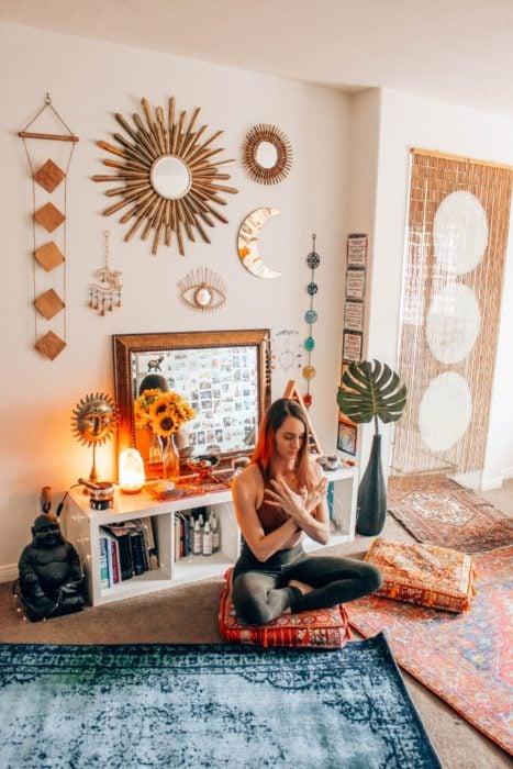 Chica con leggings y top deportivo sentada en un tapete meditando frente a su computadora