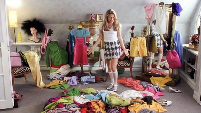 Chica dentro de su habitación con la ropa en el suelo tratando de organizar su armario