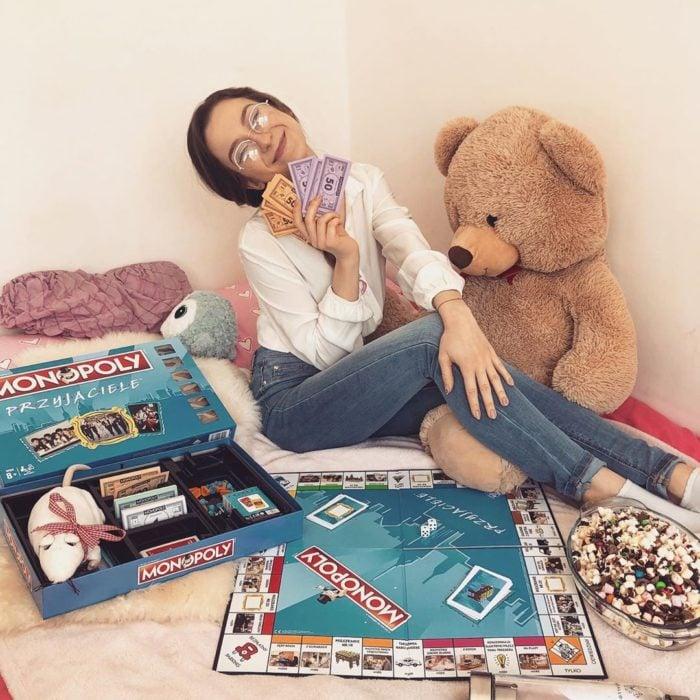 Chica sentada sobre una cama jugando con un tablero de Monopoly y sosteniendo billetes de papel de colores purpura