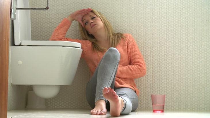 Mujer sentada en el piso del baño