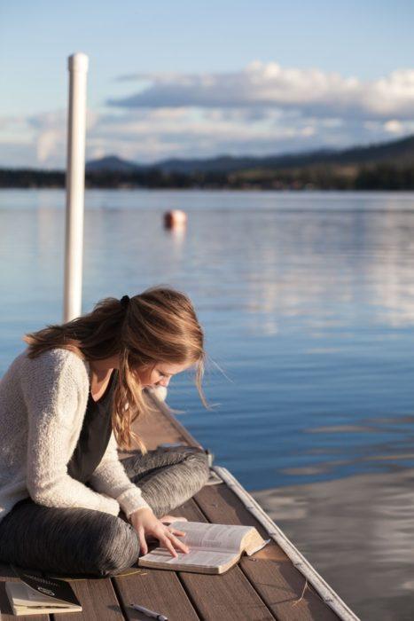 Chica leyendo en el muelle