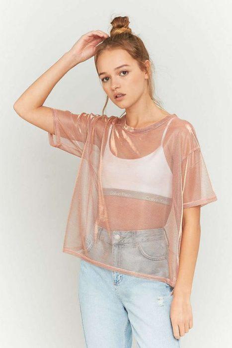 Chica usando top blnaco y blusa de transparencias en tono rosado