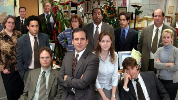 Elenco de la serie The Offic sentados frente a un escritorio de madera
