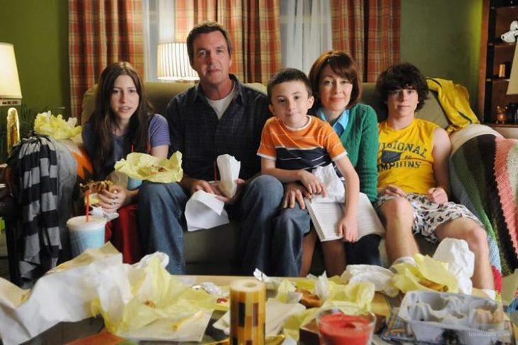 Elenco de la serie de Fox, The Middle sentados en un sillón frente a una mesa con frituras