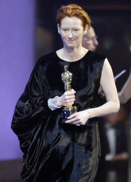 Tilda Swinton con vestido negro de una sola manga sosteniendo una estatuilla de los premios Óscar