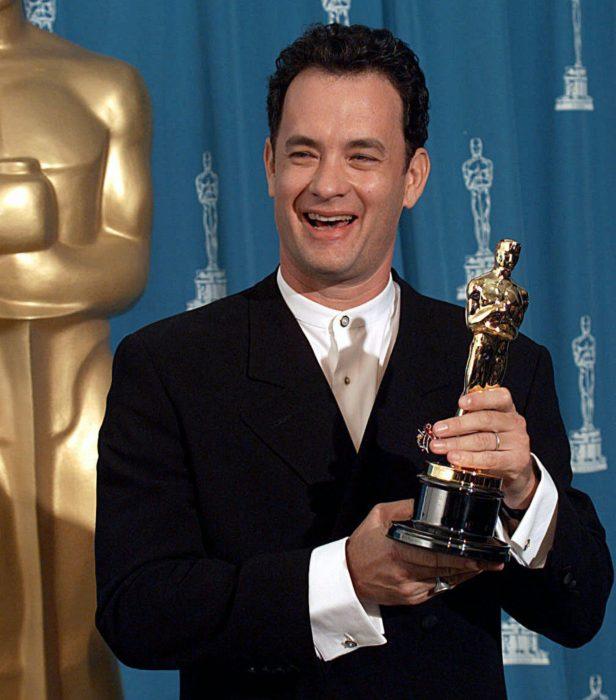 Tom Hanks sonriendo en la entrega de lso premios óscar y sosteniendo una estatuilla ganadora