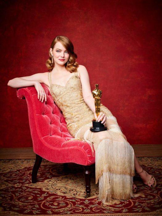 Emma Stone sentada en un sofá rojo con un vestido doradod sosteniendo una estatuilla al óscar