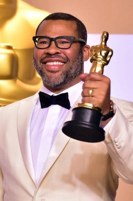 Jordan Peele sosteniendo una estatuilla de los premios Óscar, llevando un saco dorado con camisa blanca