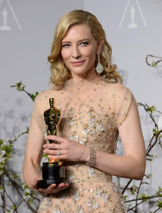 Cate Blanchett llevando u vestido dorado con transparencias sosteniendo una estatuilla al óscar