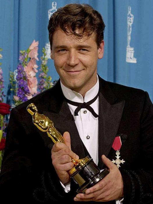 Russell Crowe con traje sastre negro sosteniendo una estatuilla de los premios óscar
