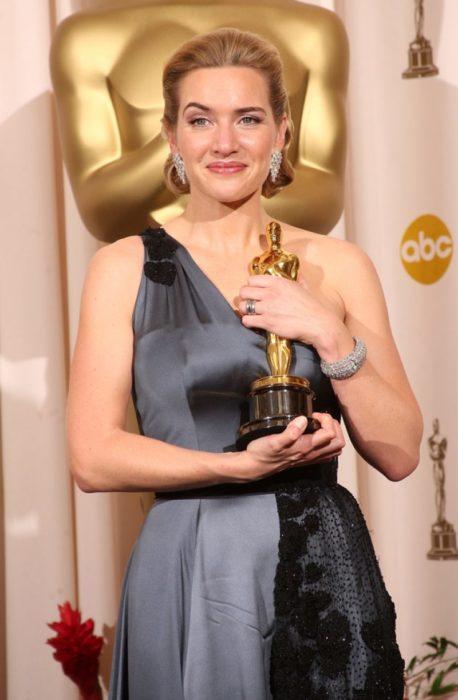 Kate Winslet so un vestido a tirantes anchos en tono gris sosteniendo una estatuilla a los premios Óscar