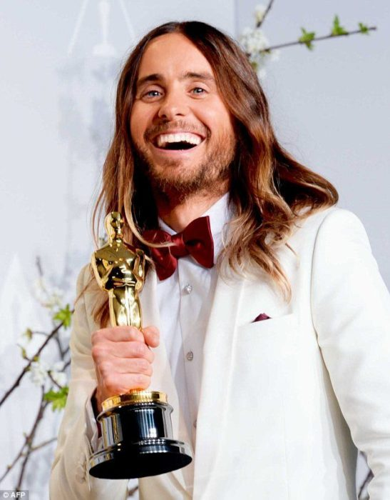 Jared Leto con saco blanco, sosteniendo una estatuilla de los premios Óscar