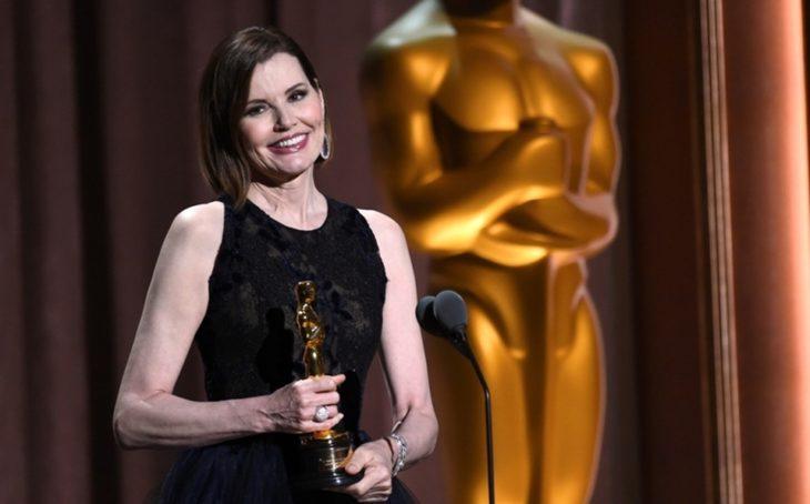 Geena Davis frente a un microfono con vestido negro sosteniendo una estatuilla al Óscar