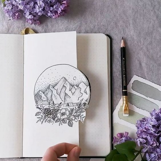 Libreta decorada con una media portada y el dibujo de un paisaje de montañas