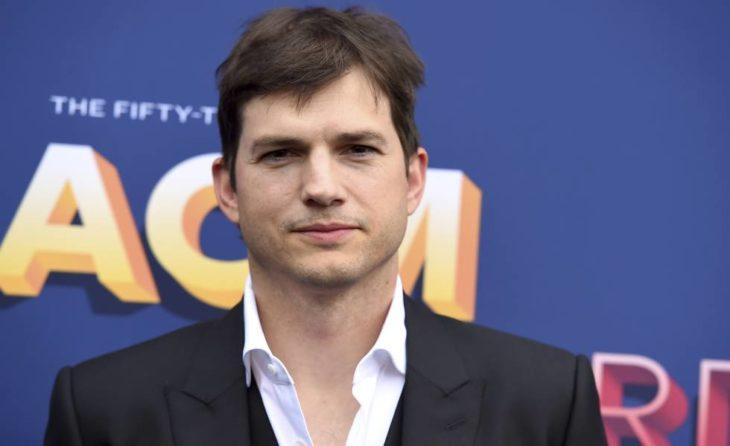 Ashton Kutcher llevando saco negro y camisa blanca mirando hacia el frente