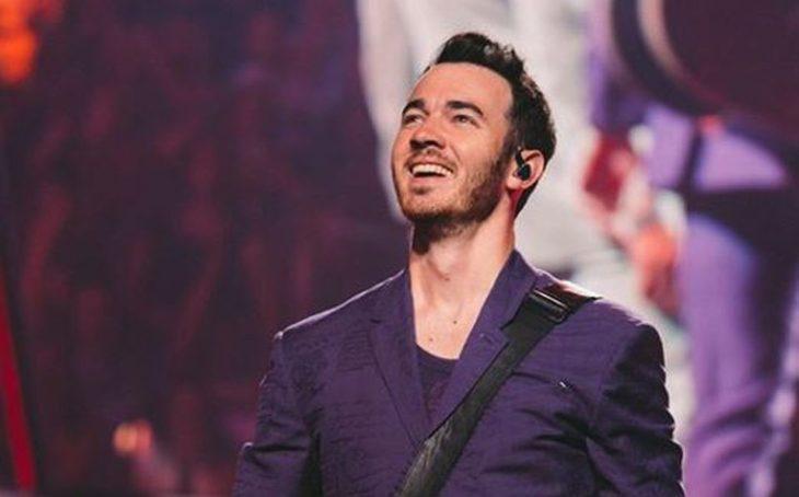 Kevin Jonas sonriendo ligeramente y mirando hacia arriba