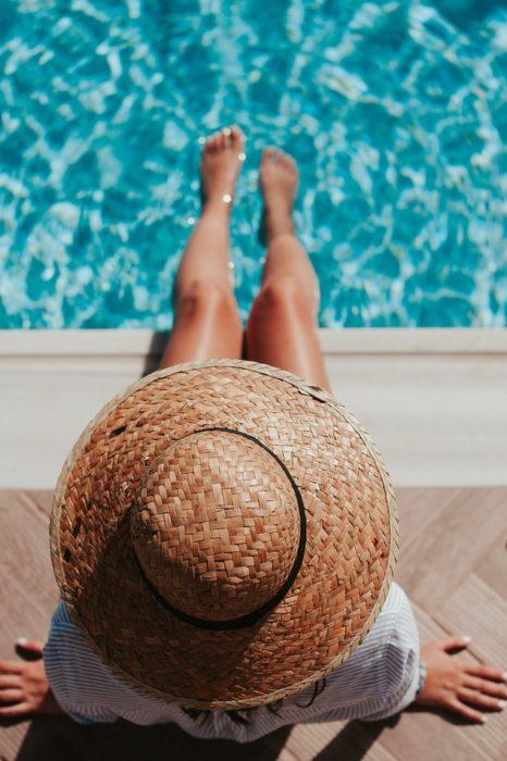 Chica con los pies dentro de la piscina