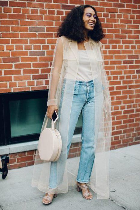 Chica usando jeans y top blnaco con un ensamble de transparencia color hueso