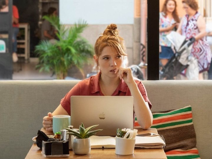 Valeria sentada en una mesa de la cafetería mientras escribe