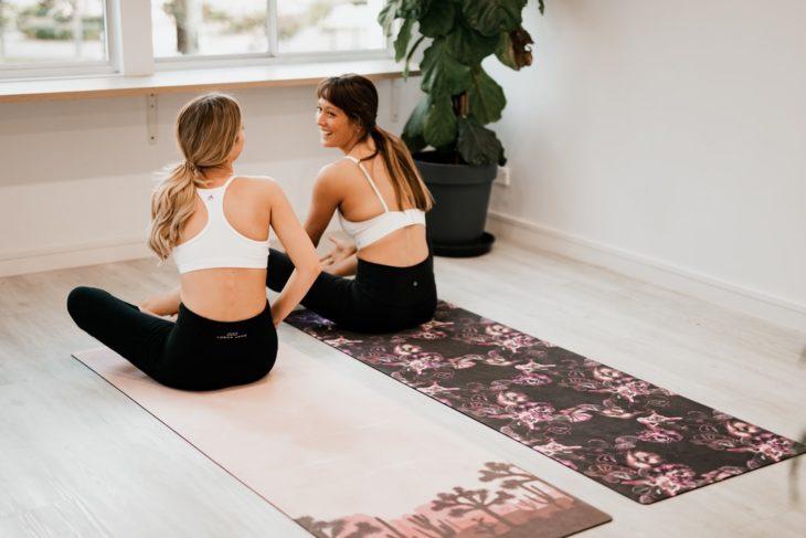 Amigas practicando ejercicio en mat de yoga