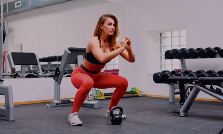 Mujer realizando sentadillas con ropa deportiva