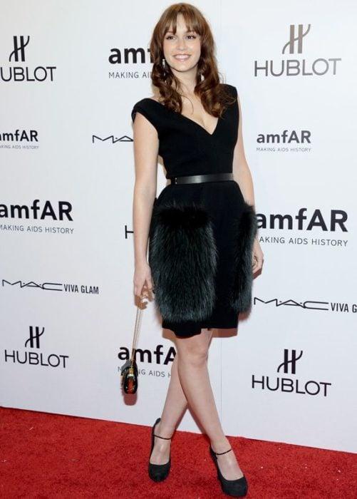 Leigton Mester usando un vestido un vestido negro con peluchito ne la falda y escote V