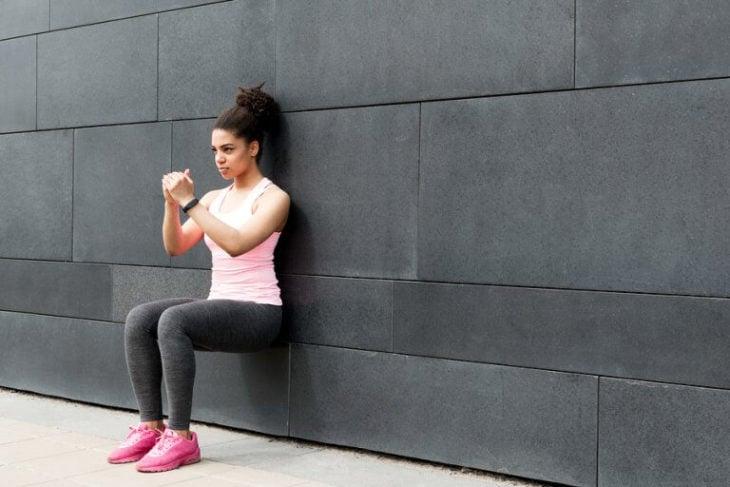 Chica realinzando sentadillas apoyada en la pared