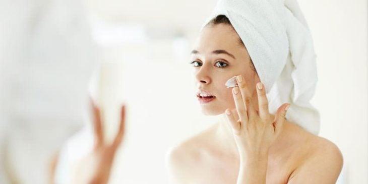 Mujer hidratando su rostro