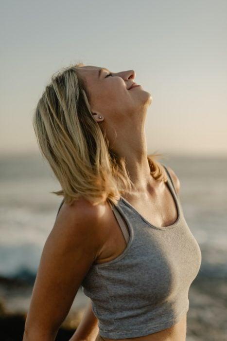 Mujer respirando profundo y feliz