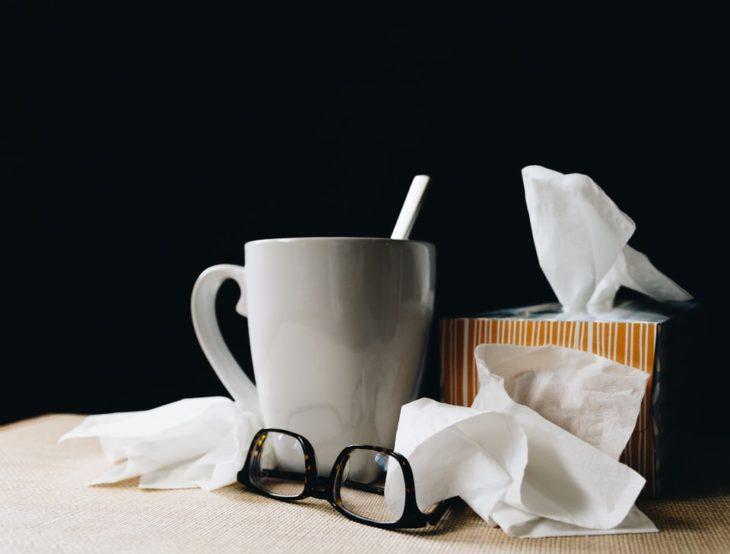 taza de té, pañuelos y lentes