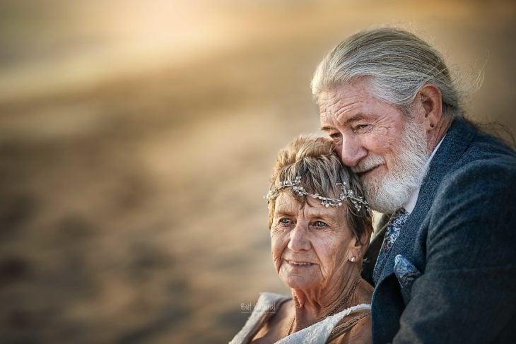 Fotografía por Abigail's Collection & The Groom's Room, pareja de abuelitos abrazados a la orilla del mar