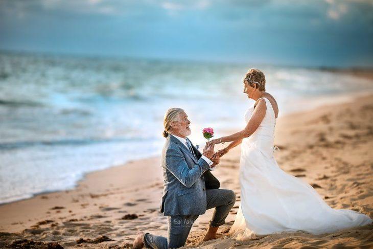 Fotografía por Abigail's Collection & The Groom's Room, pareja de abuelitos regalándose flores a la orilla del mar