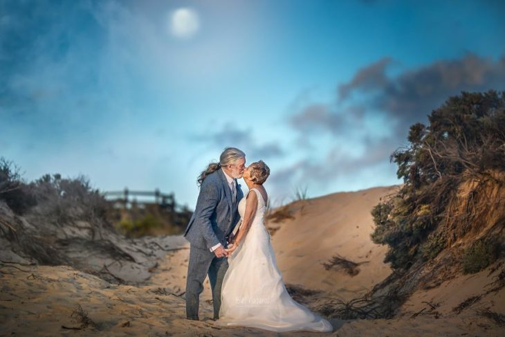 Fotografía por Abigail's Collection & The Groom's Room, pareja de abuelos besándose en la playa