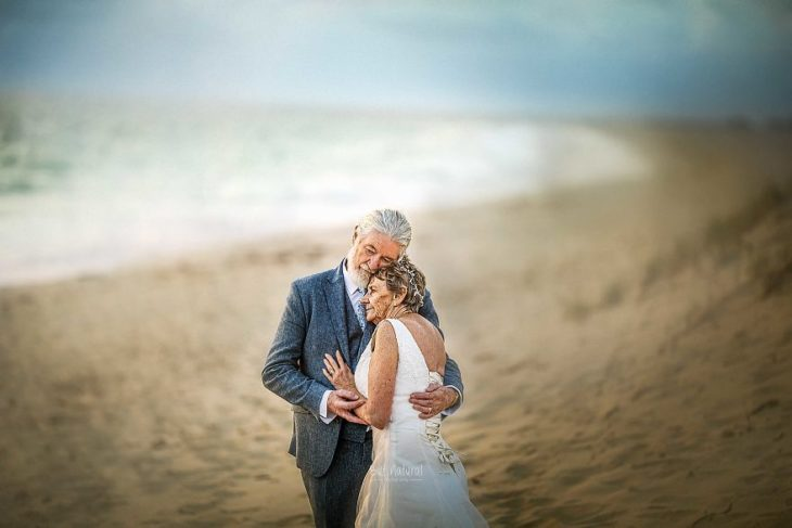 Fotografía por Abigail's Collection & The Groom's Room, pareja de abuelos abrazados en la playa mirando el mar