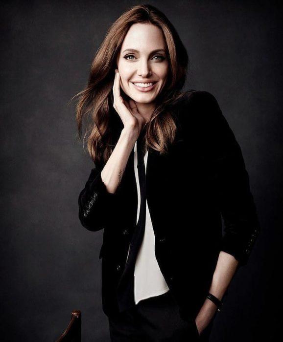 Angelina Jolie usando outfit negro con camisa clara