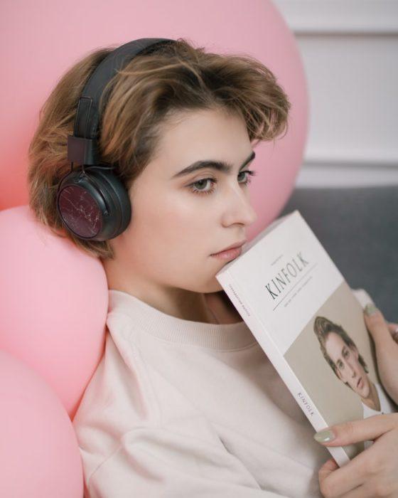 Chica escuchando música y con un libro en manos