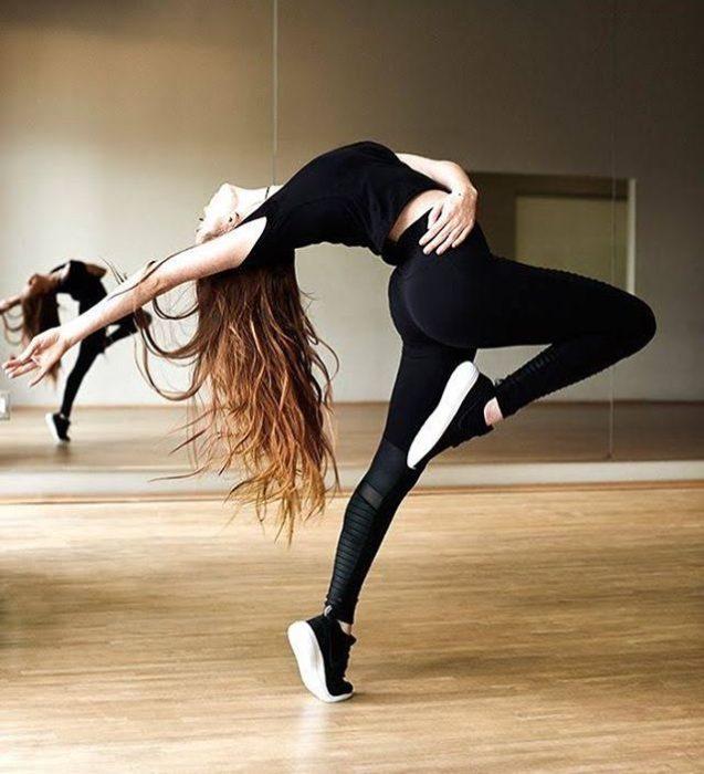 Chica en ropa deportiva practicando posiciones de ballet