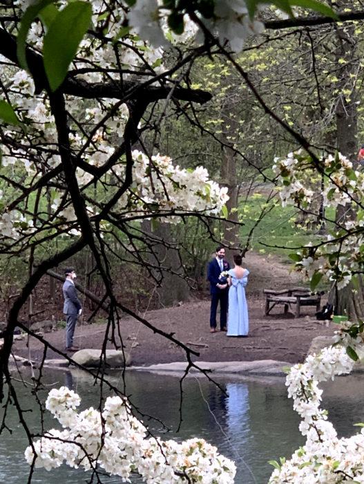 Parejas se casan en medio de cuarentena por coronavirus; esposos en un lago con árboles en flor