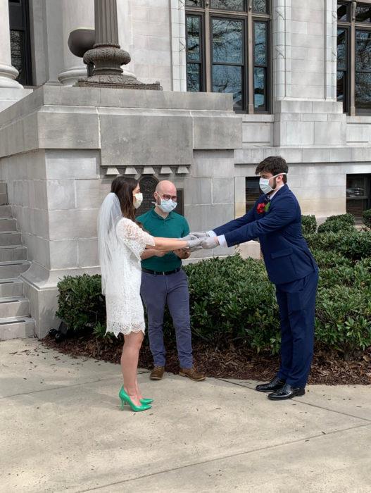 Parejas se casan en medio de cuarentena por coronavirus; esposos con cubrebocas tomados de la mano, mujer con vestido corto de novia y zapatillas verdes, hombre con traje de estir azul marino