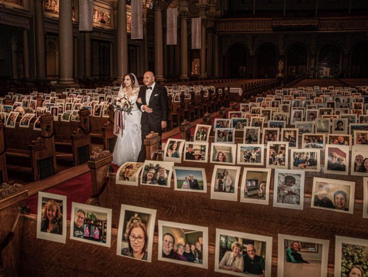 Parejas se casan en medio de cuarentena por coronavirus; esposos caminando en pasillo de iglesia con fotos de sus invitados en las bancas