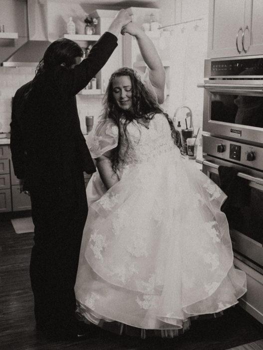 Parejas se casan en medio de cuarentena por coronavirus; esposos bailando en la cocina, hombre con traje y mujer con vestido de novia