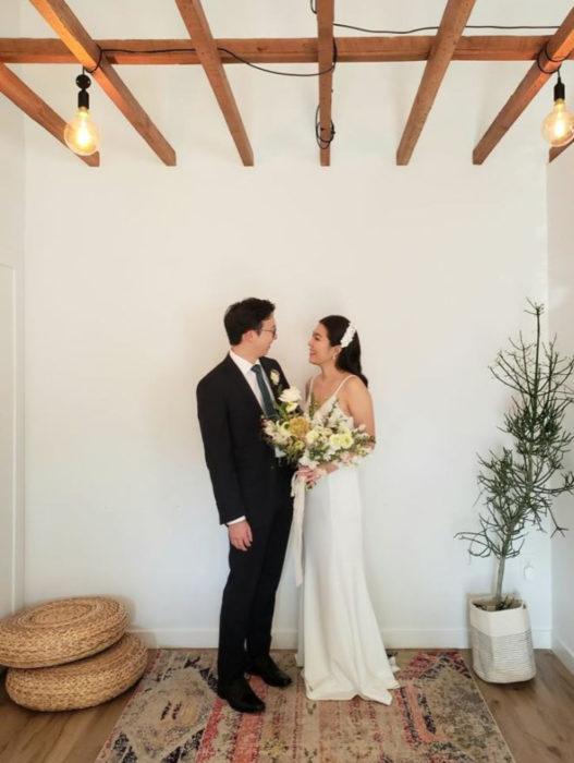 Parejas se casan en medio de cuarentena por coronavirus; hombre con traje negro, mujer con vestido de novia blanco