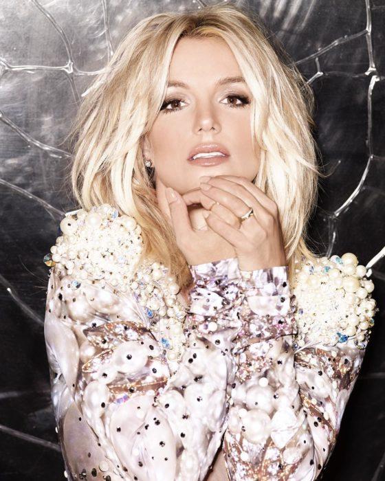 Britney Spears posando para una fotografía, usa un vestido rose gold y cabello suelto