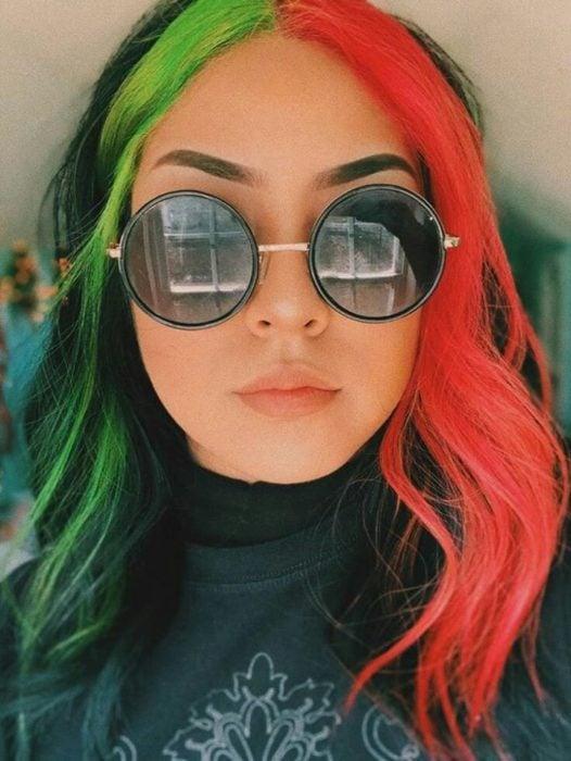 Chica con lentes grandes circulares lleva mechones de cabello verdes y naranjas