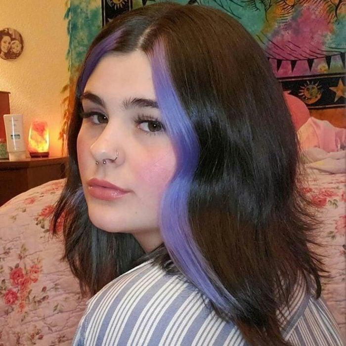 Chica con melena corta lleva mechones de cabello morados en la parte delantera de la cabeza